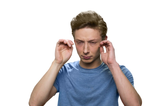 Adolescent avec maux de tête isolé sur mur blanc. adolescent mâle fatigué stressé.