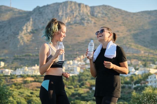 Adolescent mère et fille en vêtements de sport parler et boire de l'eau après l'entraînement