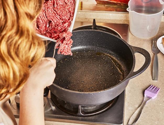 Un adolescent met du bœuf haché dans une poêle à frire pour faire des spaghettis à la bolognaise selon la recette d'internet.