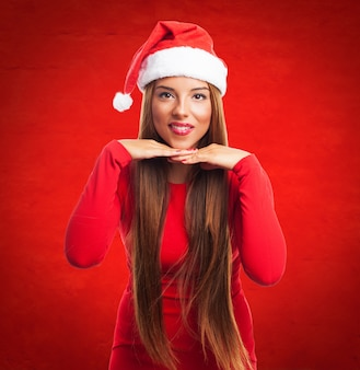 Adolescent mignon avec le chapeau de santa sur fond rouge