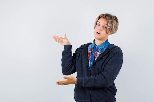 Adolescent mignon en chemise, sweat à capuche montrant un signe de grande taille et se demandant, vue de face.