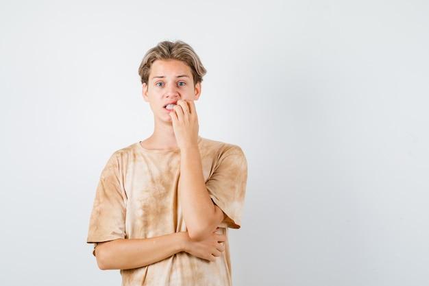 Adolescent mignon gardant la main près de la bouche en t-shirt et ayant l'air troublé. vue de face.