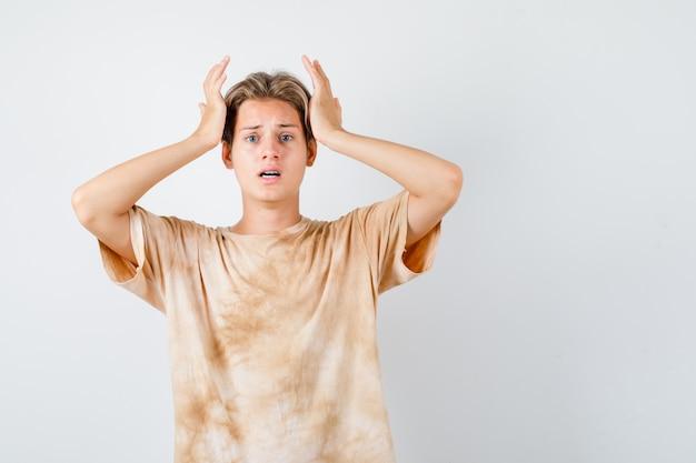 Adolescent mignon gardant les mains sur la tête en t-shirt et ayant l'air troublé. vue de face.
