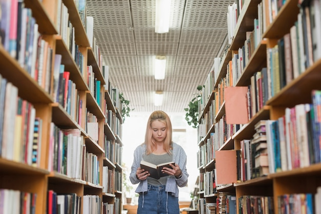 Adolescent mignon lisant entre les étagères