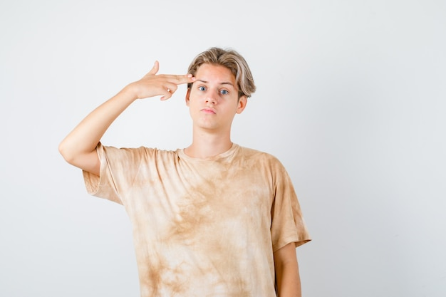 Adolescent mignon montrant un geste de suicide en t-shirt et ayant l'air déprimé, vue de face.
