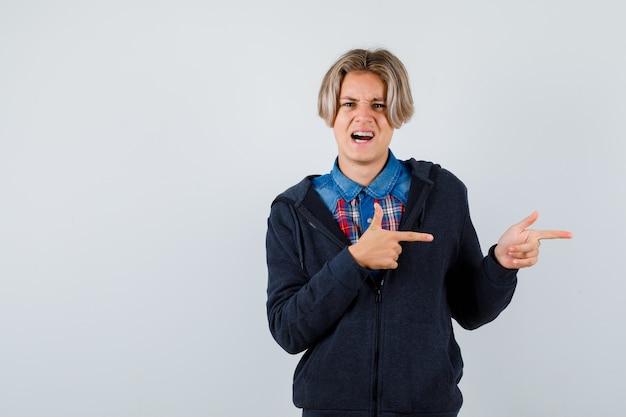 Adolescent mignon pointant vers la droite dans une chemise, un sweat à capuche et ayant l'air nerveux. vue de face.