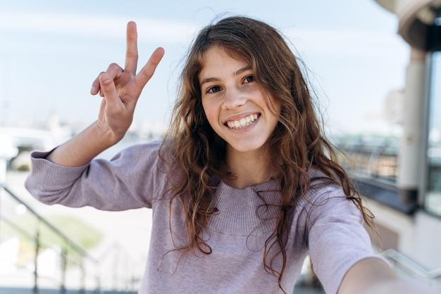 Adolescent mignon et positif tenant un appareil photo, regardant droit. la belle fille, souriant sincèrement sur le fond de la ville, montre un signe de victoire