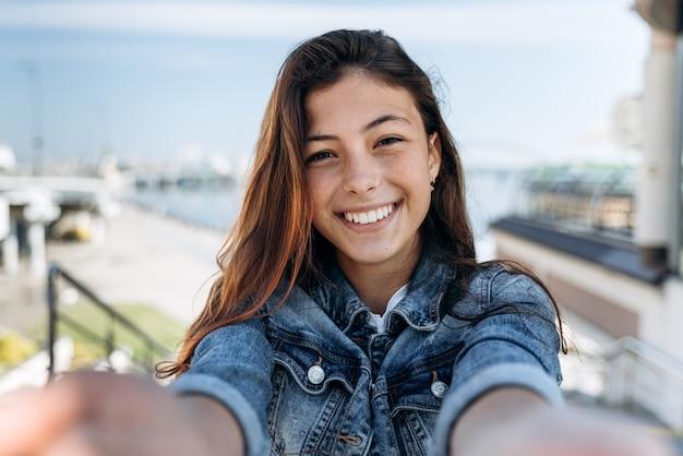 Adolescent mignon et positif tenant un appareil photo, regardant droit. belle fille souriant sincèrement sur le fond de la ville