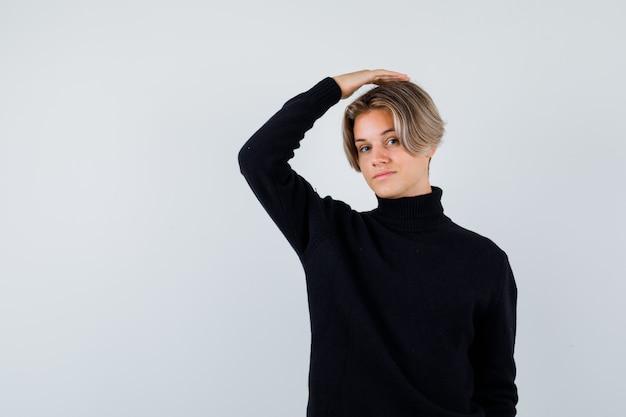 Adolescent mignon en pull à col roulé noir avec la main sur la tête et l'air intelligent