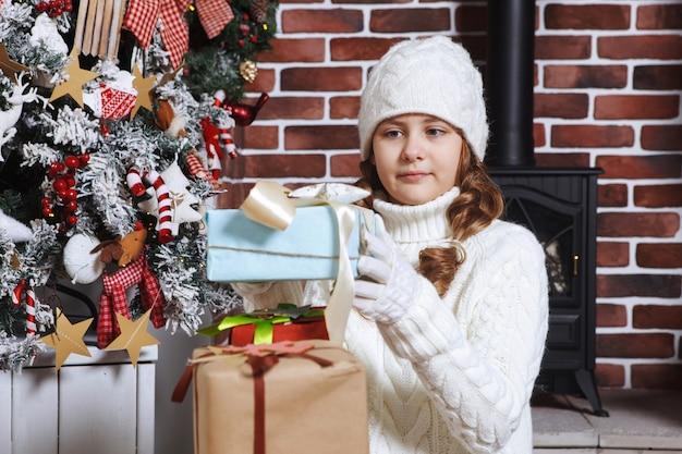 Un adolescent mignon a un sapin de noël devant une pile de coffrets cadeaux