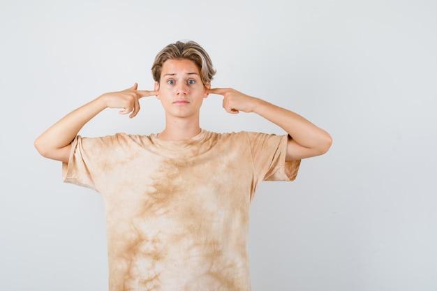 Adolescent mignon en t-shirt se bouchant les oreilles avec les doigts et ayant l'air effrayé, vue de face.