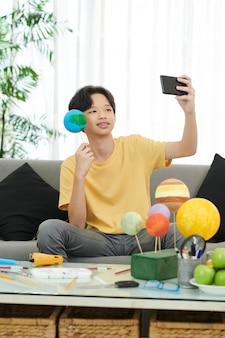 Un adolescent avec un modèle en polystyrène de la terre qu'il a fait en prenant une photo pour ses médias sociaux