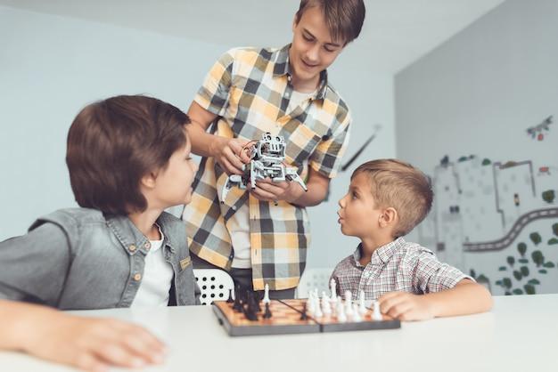 Adolescent montrant un robot à deux garçons assis.