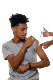 Un adolescent montre l'autocollant après avoir été vacciné isolé sur fond blanc