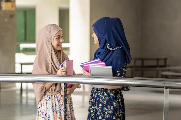 Un adolescent musulman tient des livres et discute