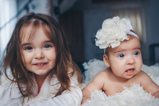 Adolescent avec un nouveau-né jouant ensemble. enfants heureux: soeurs gisant sur le sol sur fond blanc.