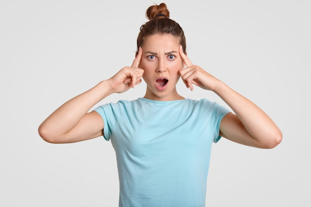 Un adolescent oublieux choqué garde l'index sur les tempes, garde la bouche largement ouverte, vêtu d'un t-shirt décontracté, pose contre le blanc. concept de personnes, expressions faciales et émotions