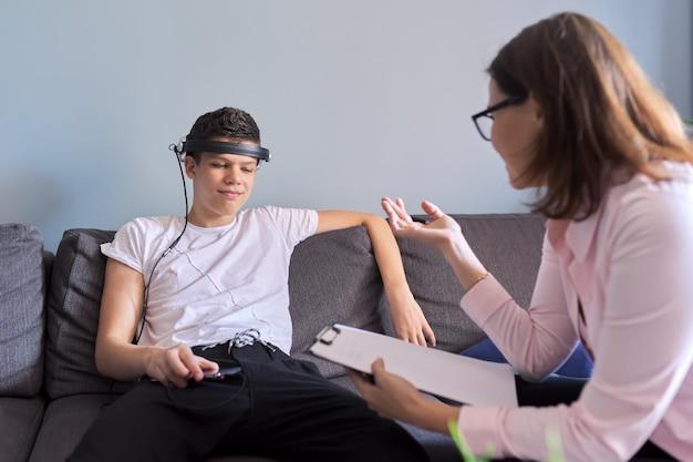 Un adolescent parle à un psychologue professionnel au bureau, une séance de thérapie individuelle pour un adolescent avec un médecin. difficultés de l'adolescence, santé mentale, vie sociale de l'adolescent
