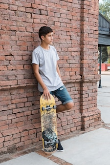 Adolescent, penchant, mur, brique, tenue, skateboarding, regarder loin