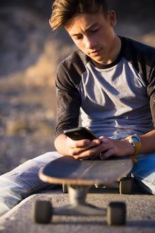 Adolescent à la plage assis sur un mur en utilisant ses téléphones avec sa planche à roulettes - garçon portant des jeans concentré sur le social ou jouant à des jeux vidéo