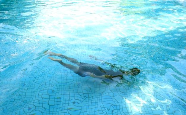 Adolescent plongée dans la piscine le jour de soleil