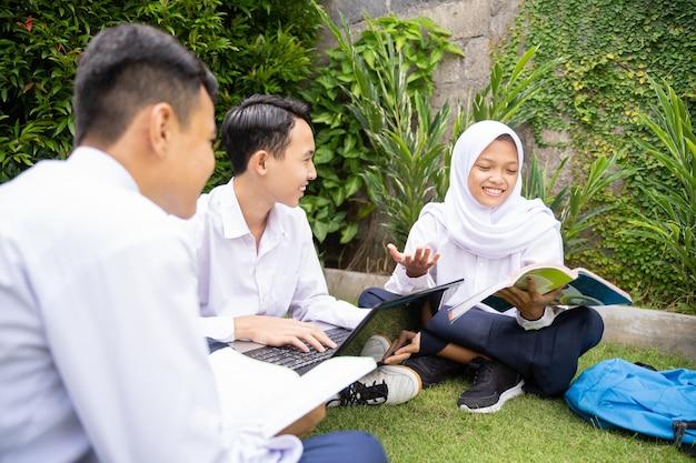 Un adolescent portant un foulard et deux adolescents en uniforme scolaire utilisant un ordinateur portable et un livre pendant qu'ils...