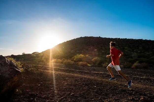 Un adolescent qui court seul et isolé dans les montagnes ou la colline écoutant de la musique pour être en forme et en bonne santé - coucher de soleil et ciel magnifique - mode de vie et concept de jogger