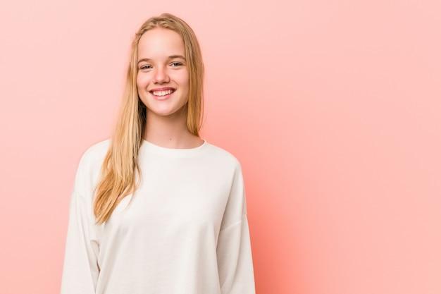 Adolescent de race blanche debout contre un mur rose