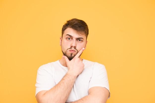 Adolescent réfléchi avec une barbe écailles sa barbe sur jaune