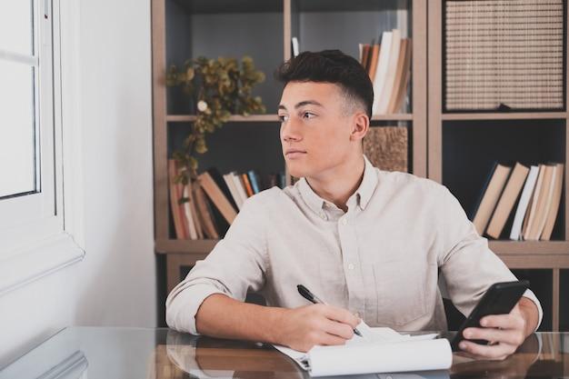 Adolescent réflexif caucasien regardant l'écran d'un ordinateur portable, réfléchissant au travail, homme d'affaires indépendant travaillant dans un projet difficile. personne de sexe masculin se préparant à la maison dans le bureau à l'intérieur.