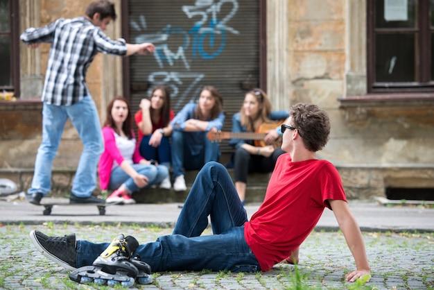 Adolescent en regardant son ami sur la planche à roulettes