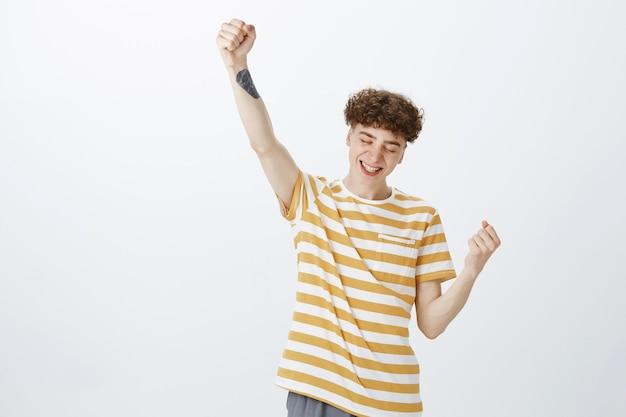 Adolescent réussi et triomphant posant contre le mur blanc