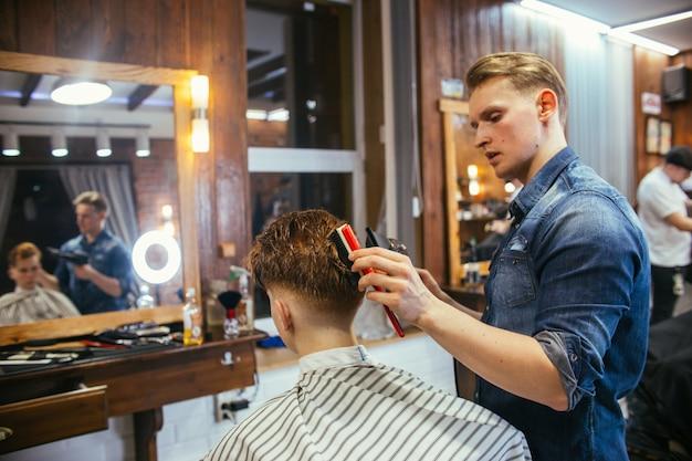 Adolescent rousse coupe de cheveux coiffeur dans le salon de coiffure.