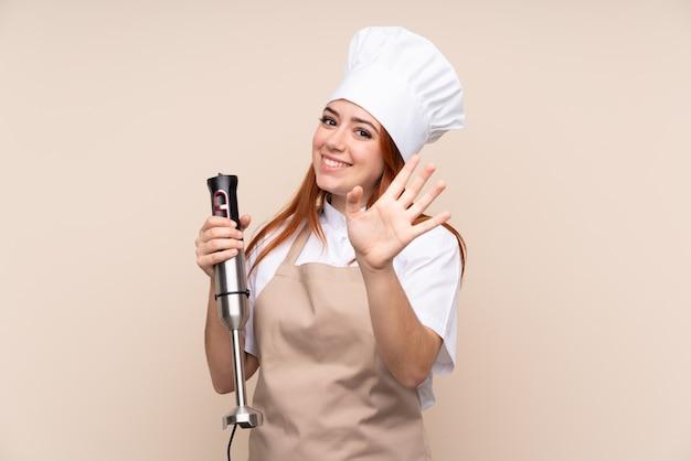 Adolescent rousse femme à l'aide d'un mélangeur à main saluant avec la main avec une expression heureuse