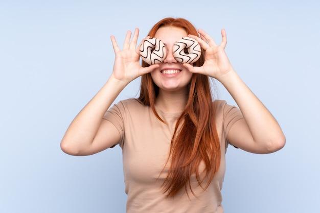 Adolescent rousse femme sur mur bleu isolé tenant des beignets dans les yeux