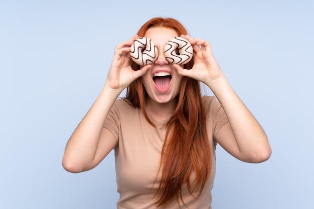 Adolescent rousse femme tenant des beignets dans un œil