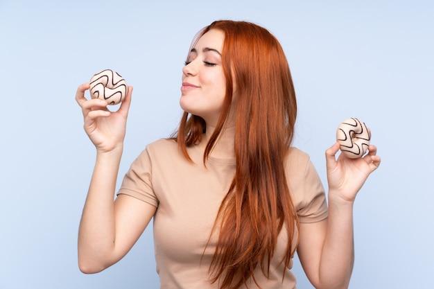 Adolescent rousse femme tenant des beignets avec une expression heureuse