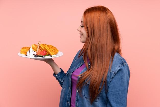 Adolescent rousse femme tenant des gaufres avec une expression heureuse