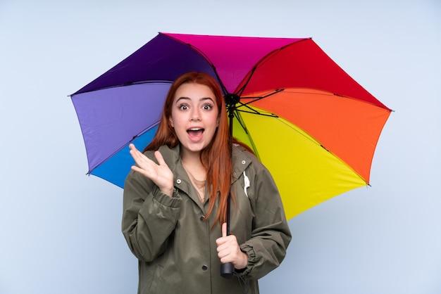 Adolescent rousse femme tenant un parapluie avec une expression faciale surprise
