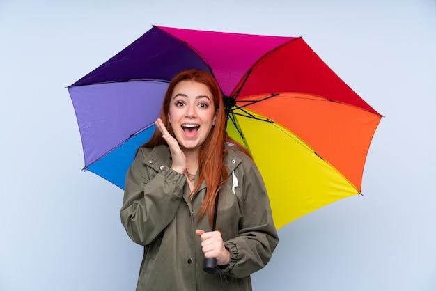 Adolescent rousse femme tenant un parapluie sur le mur bleu isolé avec expression faciale surprise