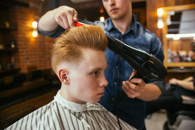 Adolescent rousse garçon coupes de cheveux coiffeur dans le salon de coiffure. coiffure rétro élégante à la mode. portrait d'un enfant avec une belle coupe de cheveux.