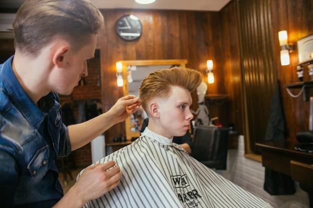 Adolescent rousse garçon coupes de cheveux coiffeur dans le salon de coiffure.