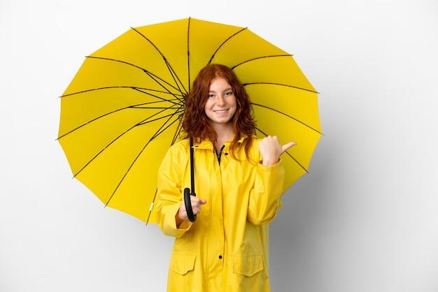 Adolescent rousse manteau imperméable et parapluie isolé sur fond blanc pointant vers le côté pour présenter un produit