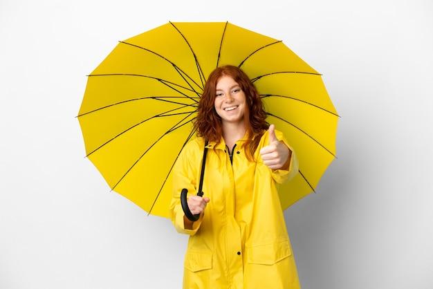 Adolescent rousse manteau imperméable et parapluie isolé sur fond blanc avec les pouces vers le haut parce que quelque chose de bien s'est passé