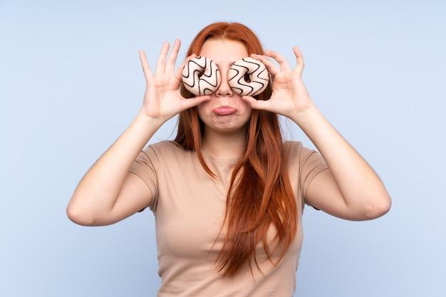 Adolescent rousse sur mur bleu isolé tenant des beignets dans les yeux avec une expression triste