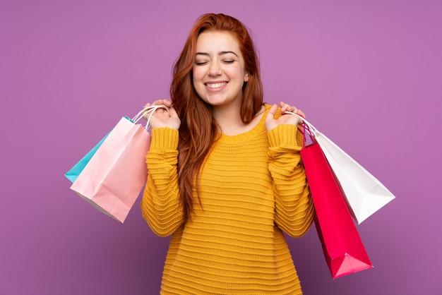 Adolescent rousse sur mur violet isolé tenant des sacs à provisions et souriant
