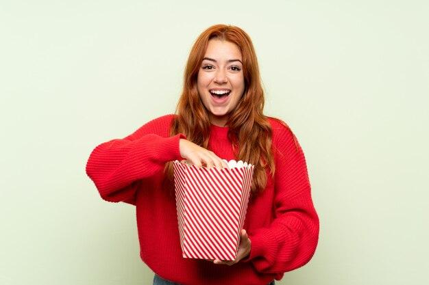 Adolescent rousse avec pull sur vert isolé tenant un bol de pop-corn