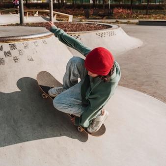 Adolescent s'amusant avec planche à roulettes dans le parc