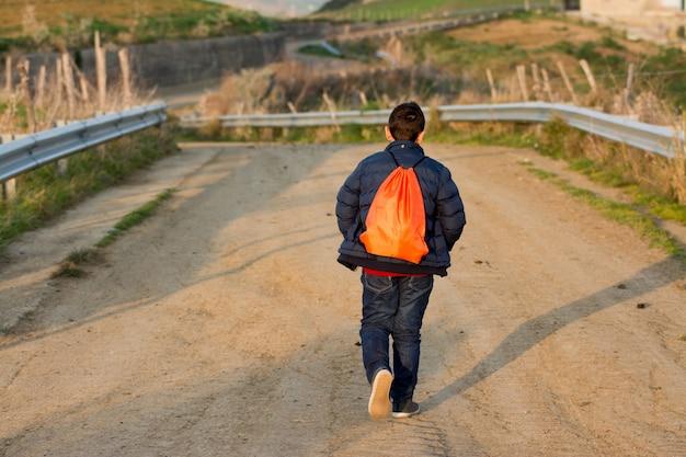 Adolescent s'éloignant sur une route cahoteuse. concept d'évasion et d'aventure