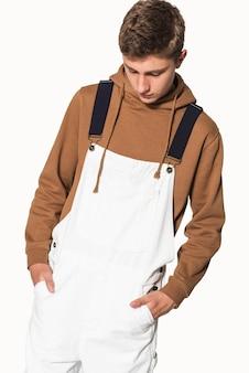 Adolescent en salopette blanche et séance photo streetwear à capuche marron